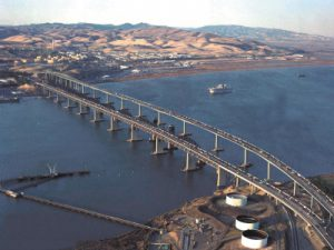 Photo of the Benicia-Martinez bridge by Ryanloney at English Wikipedia [Public domain], via Wikimedia Commons