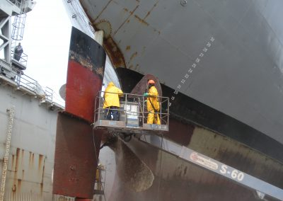Ships propeller being cleaned in a dry dock