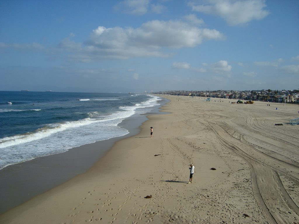 View of Hermosa Beach on a clear day with only a couple people out on the beach.