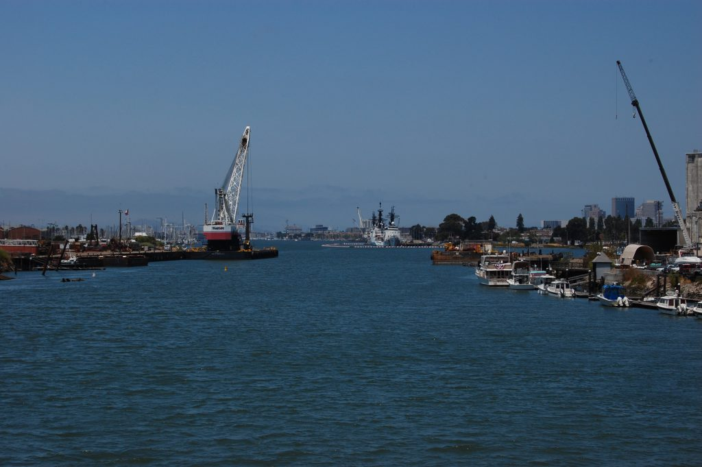 Looking down the Alameda Tidal Canal past ships and cranes.