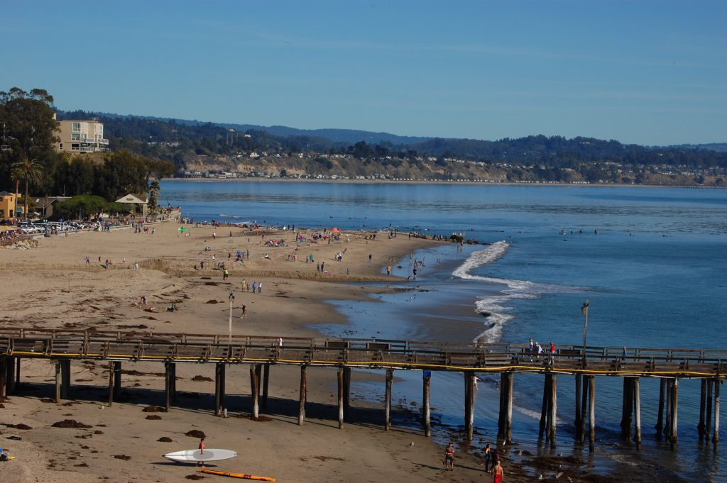 A beach and pier in Capitola with people  enjoying the day.