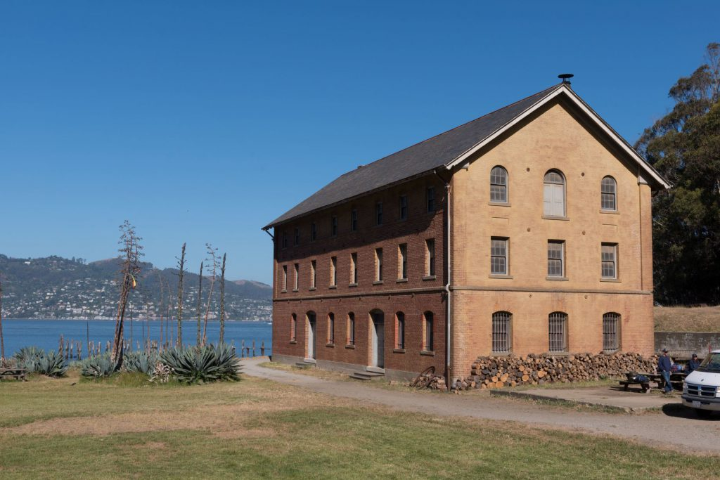 A brick building on Mare Island looking out on and across the water. Giant agave blooming nearby.